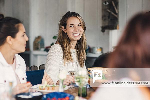 Fröhliche junge Freundinnen beim Essen am Esstisch während der Mittagsparty