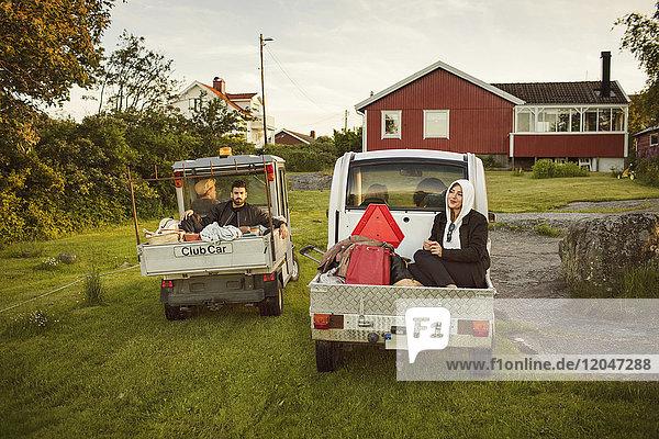 Junge Freunde sitzen in Fahrzeugen gegen Haus