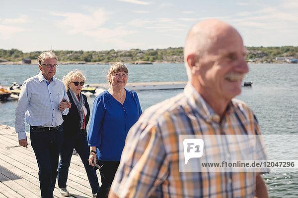 Glückliche Seniorinnen und Senioren  die im Urlaub am Pier spazieren gehen.