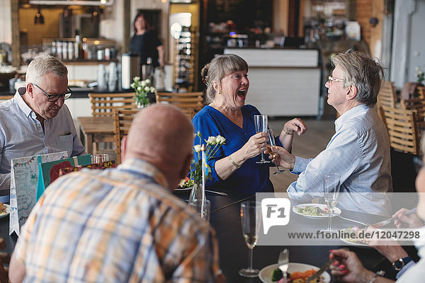 Seniorenpaar Toastflöten beim Mittagessen mit Freunden im Restaurant