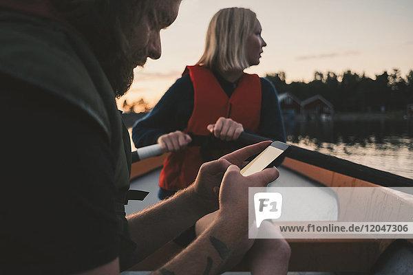 Mann mit Handy  während die Frau auf dem See rudert.