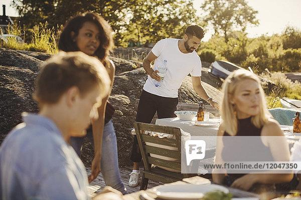 Junge multiethnische Freunde sitzen beim Tischdecken am Hafen an einem sonnigen Tag.