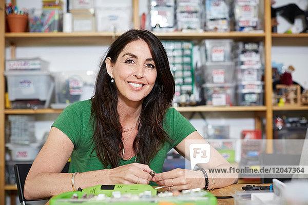 Porträt einer lächelnden  reifen Ingenieurin bei Tisch in der Werkstatt