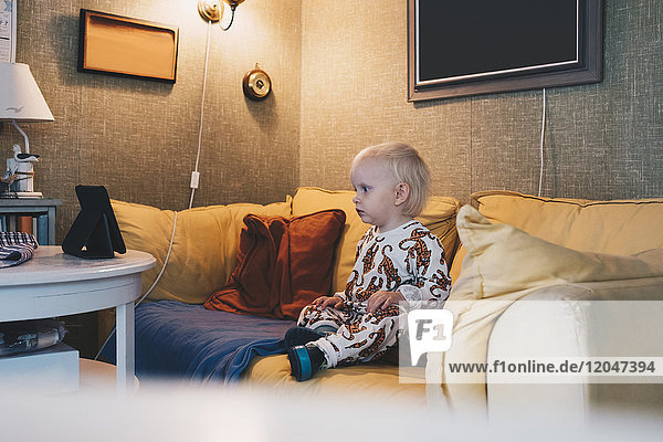 Full length of girl sitting on sofa in illuminated room at home