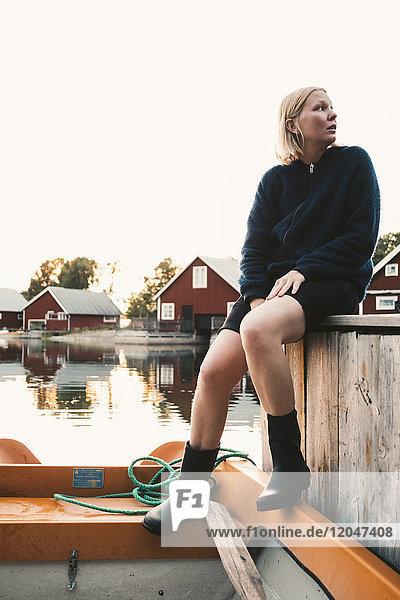 Volle Länge der nachdenklichen Frau  die im Boot in der Ferienvilla gegen den klaren Himmel sitzt.