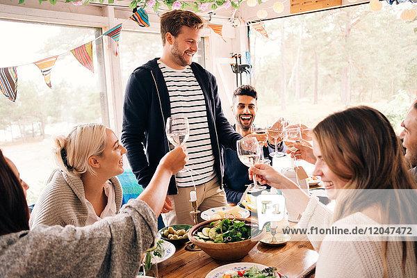 Fröhlicher Mann toastet mit Freunden bei der Mittagsparty auf Weinglas