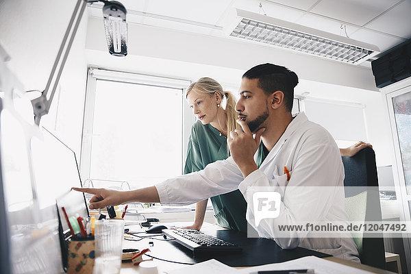 Junge männliche Ärztin zeigt auf Computerbildschirm auf Krankenschwester im Büro