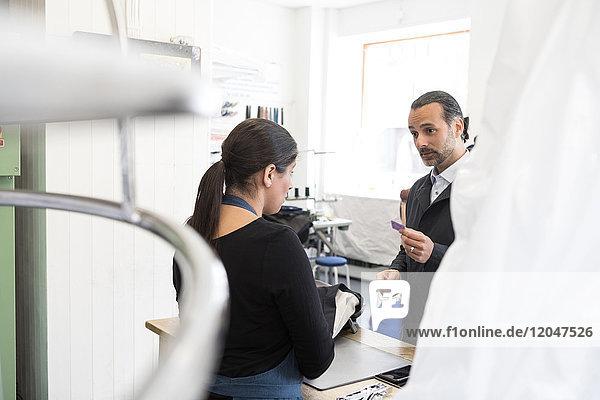 Reife Kundin und Unternehmerin im Gespräch an der Kasse im Waschsalon