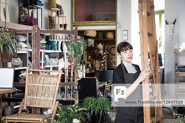 Junge Unternehmerin mit Leiter im Geschäft