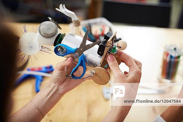 Hochwinkelansicht von Ingenieurinnen  die in der Werkstatt ein Robotermodell anfertigen