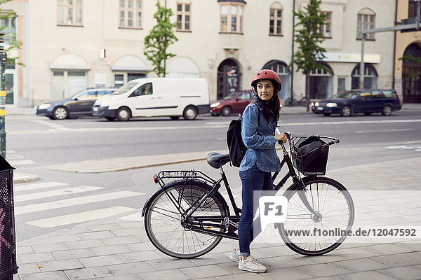 Mid adult woman standing with bicycle on sidewalk in city
