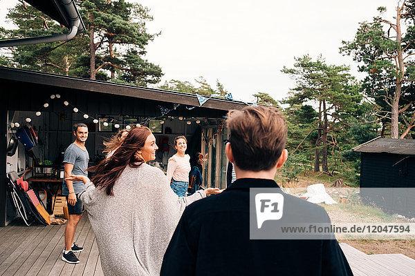 Glückliche männliche und weibliche Freunde genießen außerhalb der Hütte