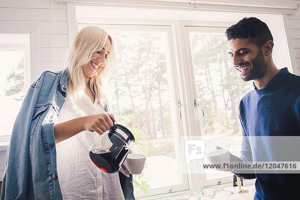 Lächelnde junge Frau  die Kaffee in die Tasse gießt  während sie zu Hause bei einem Freund steht.