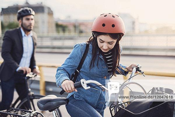 Fahrradfrau auf der Straße gegen Geschäftsmann in der Stadt