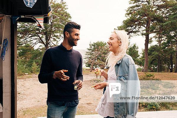 Fröhliche Freunde  die sich unterhalten  während sie Getränkegläser vor der Hütte halten.