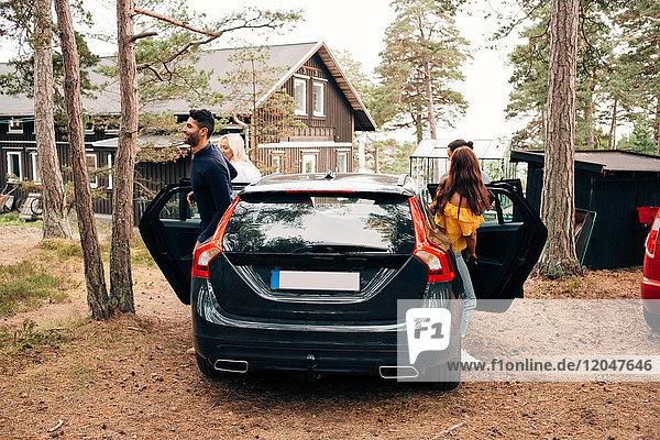 Männliche und weibliche Freunde beim Aussteigen aus dem Auto mit Hütte im Hintergrund