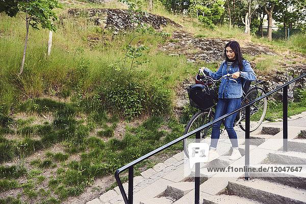 Volle Länge der Frau mit Fahrrad auf der Treppe