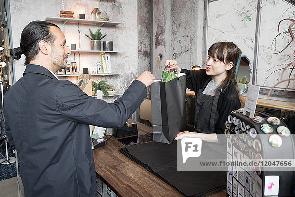 Junge Besitzerin schenkt Einkaufstasche an männlichen Kunden im Geschäft