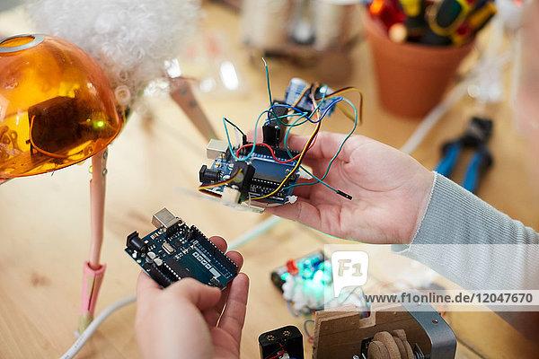 Abgeschnittene Hände einer jungen Technikerin  die elektrische Geräte am Tisch in der Werkstatt hält.