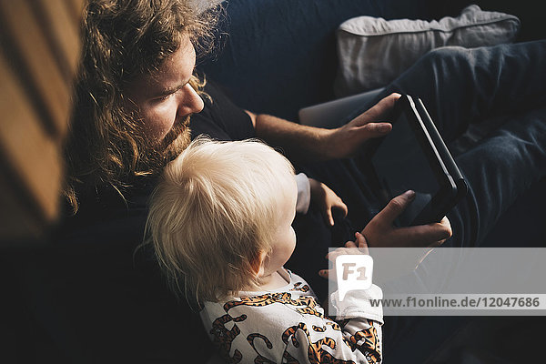 Vater zeigt dem Mädchen auf dem Sofa zu Hause ein digitales Tablett.