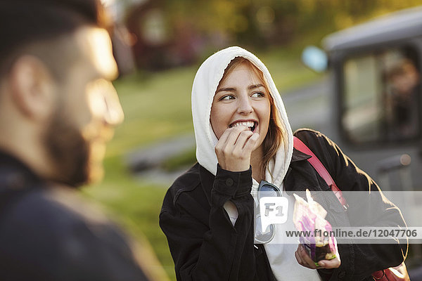Cheerful young woman eating by man while looking away