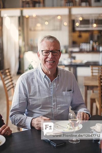 Porträt eines lächelnden älteren Mannes beim Mittagessen im Restaurant