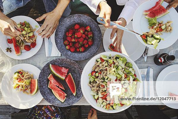 Direkt über der Aufnahme von Freunden, die an sonnigen Tagen das Mittagessen am Picknicktisch genießen.