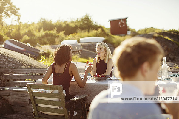 Lächelnde junge Freundinnen sitzen am Tisch und genießen das Sommeressen an einem sonnigen Tag.