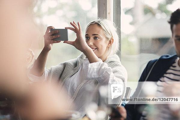 Lächelnde junge Frau fotografiert,  während sie von einem Freund am Fenster sitzt.