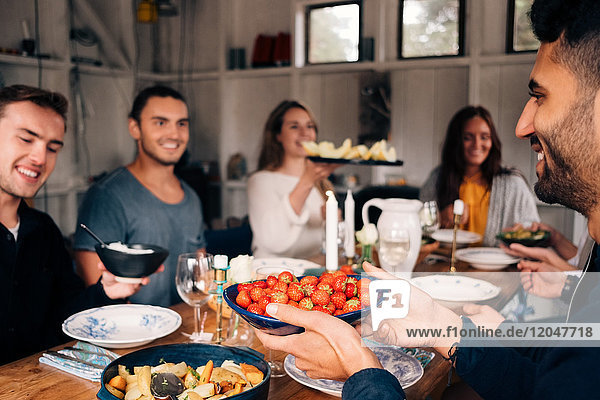Junger Mann hält eine Schale mit Erdbeeren  während er mit Freunden zur Mittagsparty sitzt.