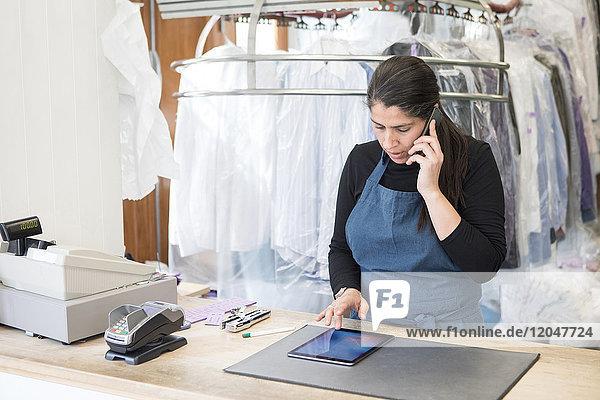 Reife Reinigungsfrau mit digitalem Tablett beim Telefonieren im Laundromat