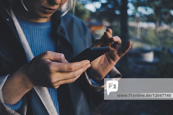 Mittelteil der Frau  die ein Smartphone benutzt  während sie im Freien steht.