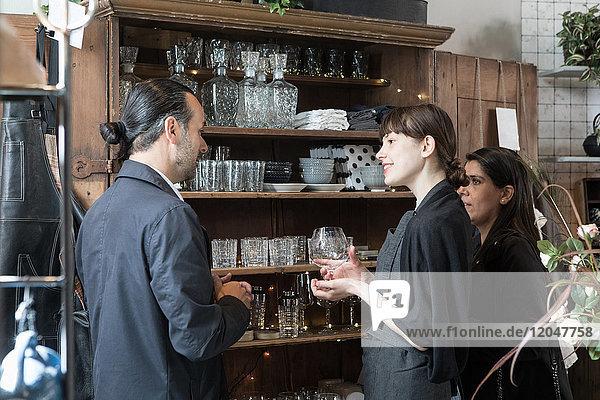 Junge Besitzerin mit Weinglas inmitten reifer Kunden im Geschäft