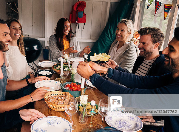 Glücklicher Mann zündet Kerze an  während er mit Freunden zum Mittagessen sitzt.