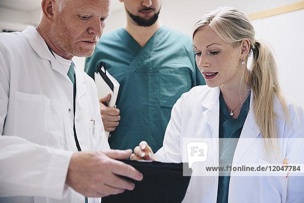 Niederwinkelansicht von Ärzten und Krankenschwestern bei der Diskussion über digitale Tabletten im Krankenhaus