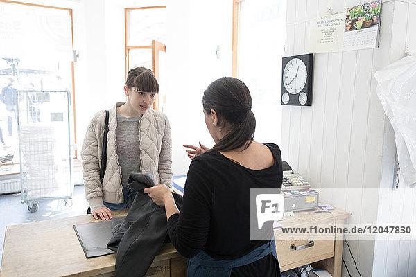 Rückansicht der reifen Waschsalonbesitzerin im Gespräch mit dem jungen Kunden an der Kasse