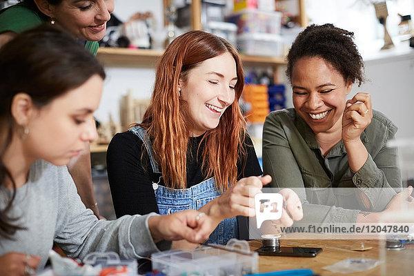 Fröhliche Ingenieurinnen bei Tisch in der Werkstatt