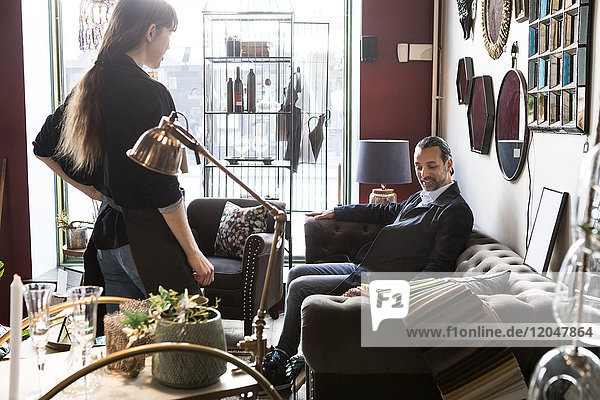 Mature male customer sitting on sofa while looking at fabric swatch with female owner standing in store