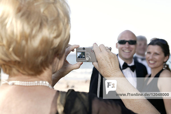 Woman Taking Couple's Portrait at Wedding