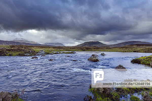 River in moor landscape with dark storm clouds with mountains in the background at Rannoch Moor in Scotland  United Kingdom