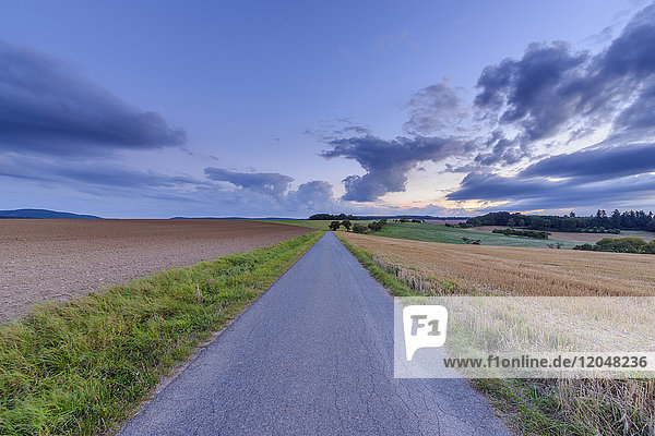 Countryside with harvested cereal field and paved laneway at dusk in summer at Roellbach in Spessart hills in Bavaria  Germany