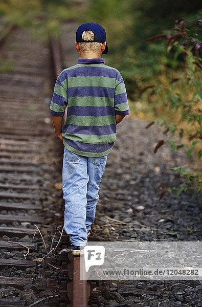 Boy Walking Along Train Tracks