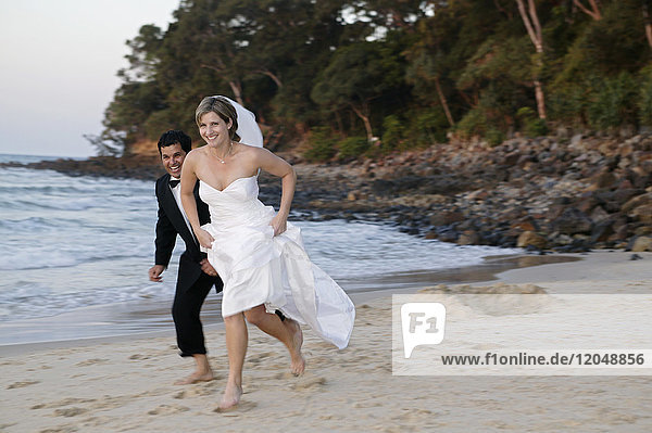 Groom Carrying Bride on Beach  Noosa Beach  Australia