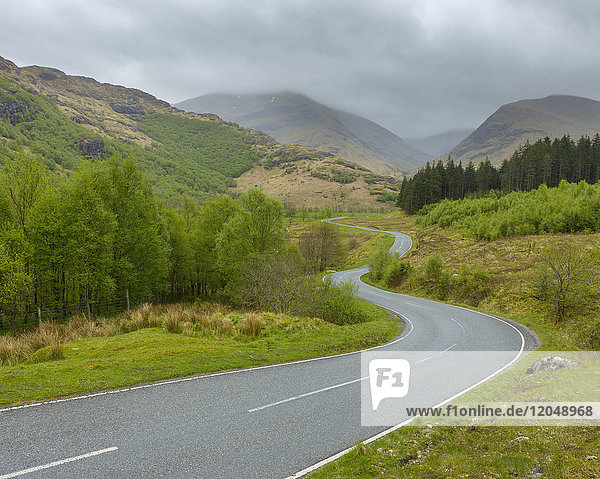 Winding country road and hills with overcast sky at Glen Nevis near Fort William in Scotland  United Kingdom