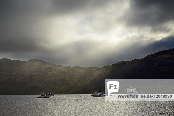 Cruise ships on lake with dramatic clouds and light at Loch Lomond in Scotland  United Kingdom