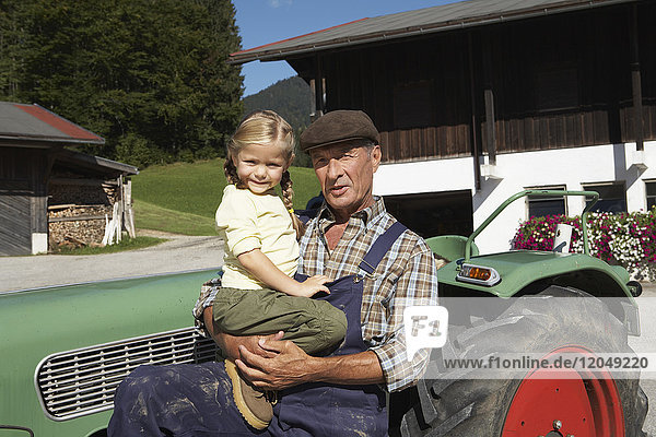 Farmer and Girl in Front of Tractor