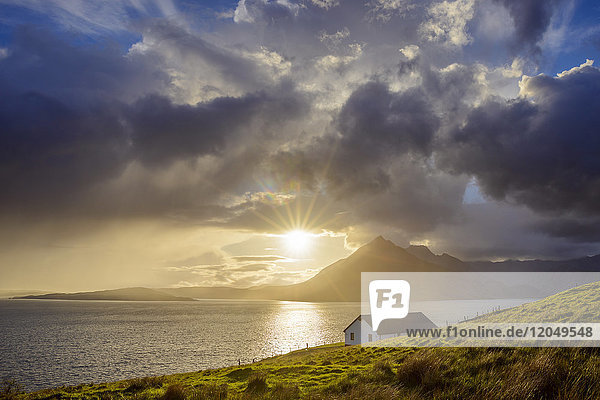 Rooftop of a house along the Scottish coast with sun shining through the clouds over Loch Scavaig  Isle of Skye in Scotland