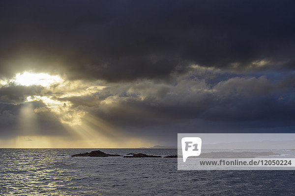 Sun shining through the storm clouds at sunrise along the Scottish coast at Mallaig in Scotland  United Kingdom