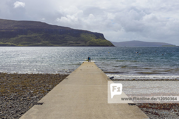 Concrete pier with couple looking at view of the sea on a sunny day on the Isle of Skye in Scotland  United Kingdom