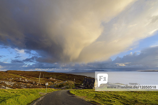 Road leading to the harbor with houses on the hillside and storm clouds over Loch Scavaig on the Isle of Skye in Scotland